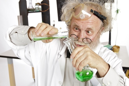 Mad senior scientist in lab concentrates on pouring green liquid into beaker  Frizzy grey hair, round glasses, lab coat, blackboard, vertical, high key, copy space