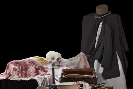 Staged crime scene in style of Jack the Ripper, with bloody corpse, knives and surgery equipment  Isolated on black background, dramatic spot lighting, copy space Stock Photo - 16962941
