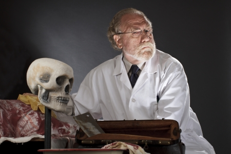 Evil lékař s chirurgickými nástroji a krvavé mrtvoly zlověstný výraz, tmavé pozadí s dramatickým nízký úhel bodové osvětlení horizontální, kopírovat prostor