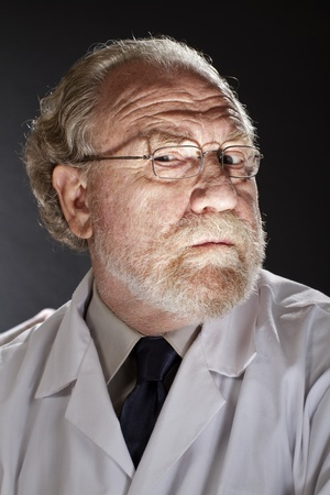 Portrait of evil doctor in lab coat and necktie with sinister expression  Dark background and dramatic low angle spot lighting create spooky shadows on face