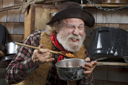cowboy man: Classic old western style cowboy with felt hat, grey whiskers, red bandana. He eats beans from a saucepan. Camp cookware and wood shingles in background.