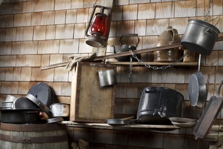 traditional outdoor cowboy kitchen with battered cookware jug lantern rough plank shelves - Cowboy Kitchen