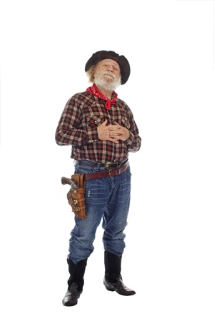 old cowboy: Classic old western style cowboy with felt hat, grey whiskers, revolver, stands clasping hands against chest. Isolated on white background, copy space, vertical. Stock Photo