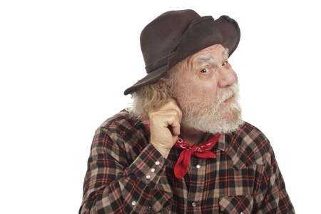 Classic old western style cowboy with felt hat and grey whiskers pulls on his ear and considers an idea. photo