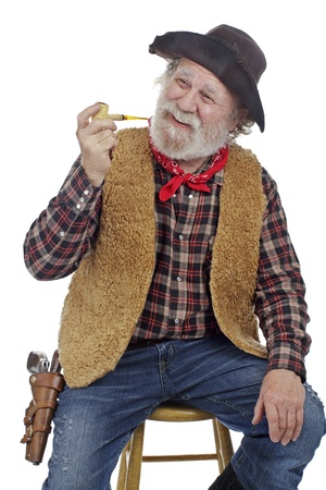 old timer: Classic old west style smiling cowboy with felt hat, grey whiskers, revolver, holds corn cob pipe and sits on stool. Isolated on white, vertical, copy space.