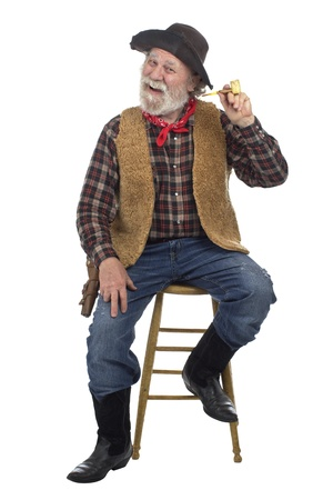 Classic old west style cheerful cowboy with felt hat, grey whiskers, revolver. He holds corn cob pipe and sits on stool. Isolated on white, vertical, copy space.