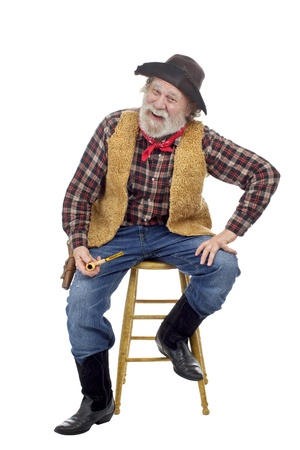 Classic old west style smiling cowboy with felt hat, grey whiskers, revolver. He sits on stool holding a corn cob pipe. Isolated on white, vertical, copy space.