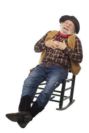 Classic old west style laughing cowboy with felt hat, grey whiskers, revolver. He relaxes leaning back in a rocking chair. Isolated on white, vertical, copy space. Stock Photo - 16980033