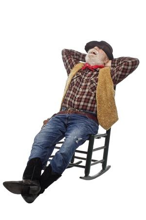 Classic old west styl smích kovboj s plstěný klobouk, šedé kníry, revolver. Relaxuje se opřel v houpacím křesle. Na bílé, vertikální, kopie prostor.