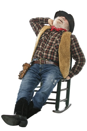 Classic old west style laughing cowboy with felt hat, grey whiskers. He relaxes leaning back in a rocking chair. Isolated on white, vertical, copy space.