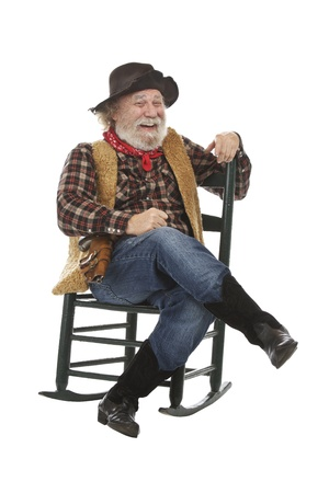 Classic old west style laughing cowboy with felt hat, grey whiskers, revolver. He sits legs crossed in a rocking chair. Isolated on white, vertical, copy space.