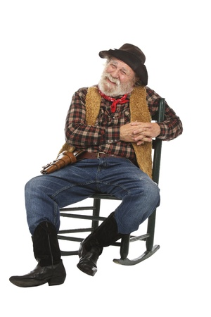 Classic old west style smiling cowboy with felt hat, grey whiskers, revolver. He relaxes in a rocking chair. Isolated on white, vertical, copy space.