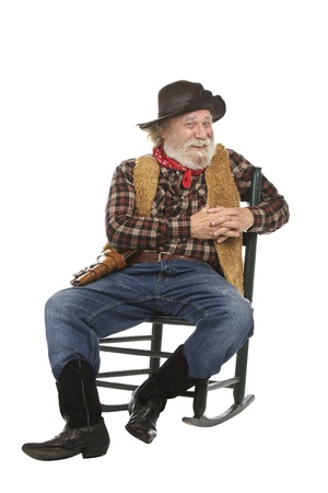 Classic old west style smiling cowboy with felt hat, grey whiskers, revolver. He sits in a rocking chair. Isolated on white, vertical, copy space. Stock Photo - 16980080