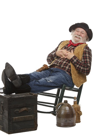 Classic old west style friendly cowboy with felt hat, grey whiskers, revolver. He leans back in a rocking chair with feet up. Isolated on white, vertical, copy space. photo