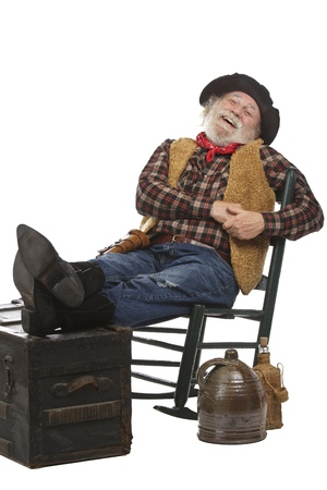 Classic old west style laughing cowboy with felt hat, grey whiskers, revolver. He leans back in a rocking chair with feet up. Isolated on white, vertical, copy space. photo