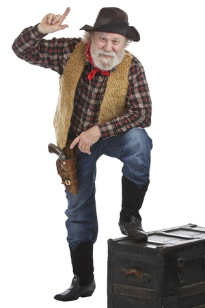 Classic old west style cowboy points up. He has felt hat, grey whiskers, revolver, and stands with one foot up on a wooden chest. Isolated on white, vertical, copy space. Stock Photo - 16963050