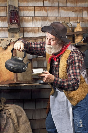 Classic old western style cowboy cook with felt hat, grey whiskers, apron. He is ready to pour tea into a white china tea cup. photo