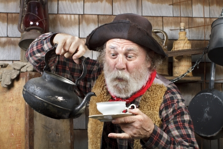 he old: Classic old western style cowboy cook with felt hat, grey whiskers, red bandana. He is ready to pour tea into a white china tea cup.