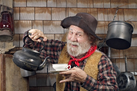 Classic old western style cowboy cook with felt hat, grey whiskers, red bandana. He is ready to pour tea into a white china tea cup.