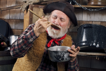 Classic old western style cowboy with felt hat, grey whiskers, red bandana. He closes eyes and savors food in a saucepan. Camp cookware and wood shingles in background. Stock Photo