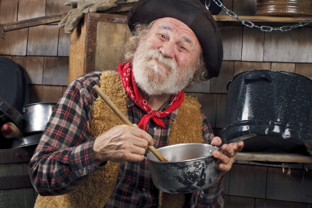 Classic old western style cowboy cook with felt hat, grey whiskers, red bandana. He stirs a saucepan with a wooden spoon. Camp cookware and wood shingles in background.