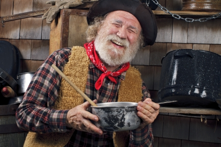 Classic old western style cowboy with felt hat, grey whiskers, red bandana. He holds a saucepan. Camp cookware and wood shingles in background.