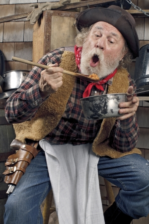western food: Classic old western style cowboy with felt hat, grey whiskers, red bandana. He sits and eats beans from a saucepan. Camp cookware and wood shingles in background.