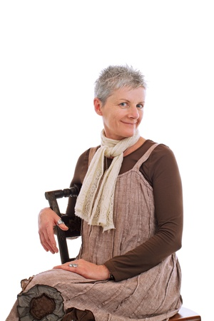 loose fitting: Smiling older woman sits sideways on chair. She wears flowered boots and brown cotton shift dress. Closeup, isolated on white background, vertical, copy space.