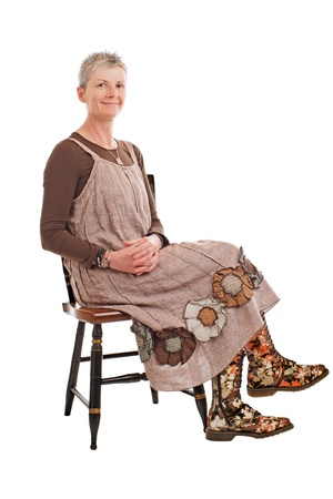 loose fitting: Smiling older woman with short gray hair sits sideways on chair, hands clasped. She wears flowered boots and brown cotton shift dress. Isolated on white background, vertical, copy space. Stock Photo
