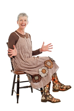 loose fitting: Laughing older woman with short gray hair sits sideways on chair with hands outspread. She wears flowered boots and brown cotton shift dress. Isolated on white background, vertical, copy space. Stock Photo