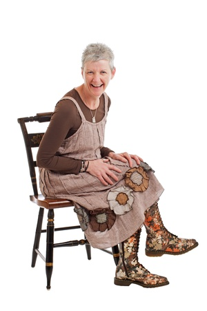 loose fitting: Laughing older woman with short gray hair sits sideways on chair and leans forward. She wears flowered boots and brown cotton shift dress. Isolated on white background, vertical, copy space.