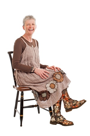 Laughing older woman with short gray hair sits sideways on chair. She wears flowered boots and brown cotton shift dress. Isolated on white background, vertical, copy space. photo