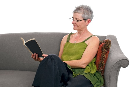 loose fitting: Senior woman relaxes seated on gray sofa and reads a paperback book. She has short gray hair and wears a loose green and black linen dress. Horizontal, isolated on white background, copy space. Stock Photo