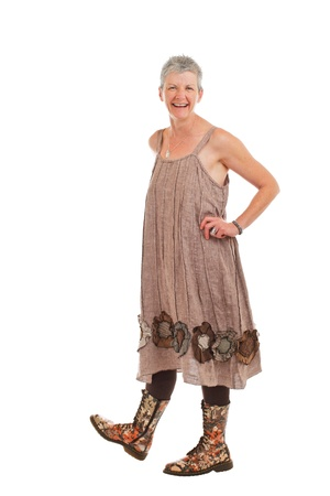 loose fitting: Cheerful friendly older woman stands in flowered boots and brown cotton shift dress. She has short gray hair. Isolated on white background, vertical.