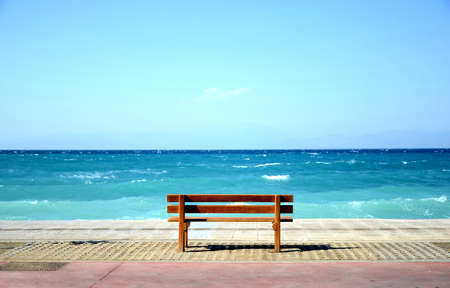 A bench on the coast, by the sea photo
