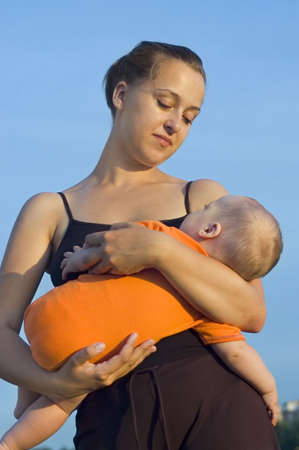 parentage: Young mother holding baby in her arms