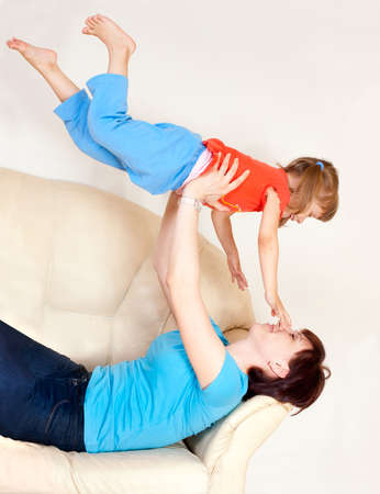 parentage: Woman playing with baby on the couch