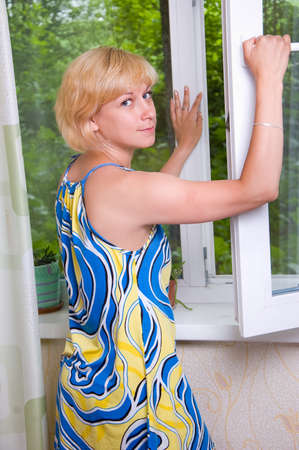 Girl airs apartment, summer heat Stock Photo