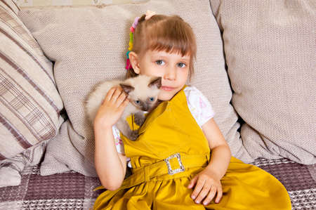 Girl petting a kitten sitting on the couch photo