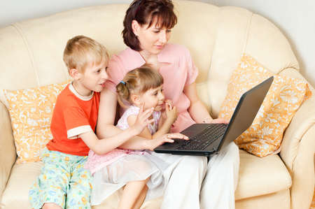 Children and their mother using a computer at home Stock Photo - 10736141