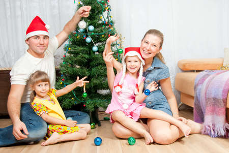 Happy family dresses up Christmas tree photo
