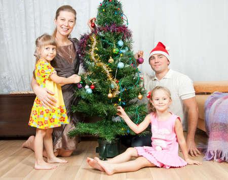 Happy family dresses up Christmas tree photo