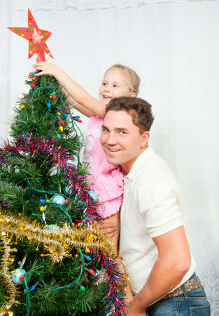 The family decorated the Christmas tree, wear the star photo