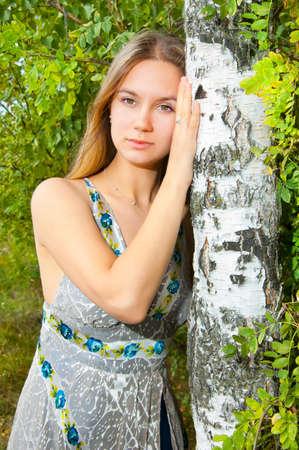 Thoughtful girl near birch trunk photo