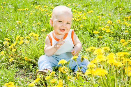 Baby children sitting on the grass in the sun photo