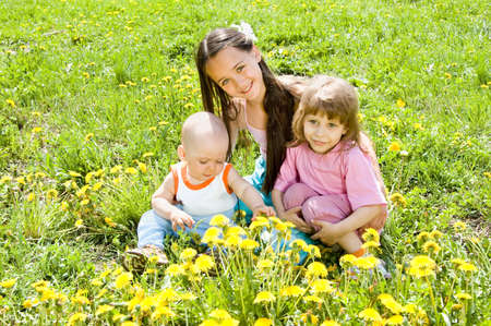Three children sitting on the grass in the sun photo