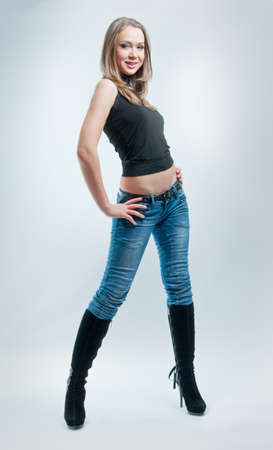 girl in jeans standing on a gray background photo