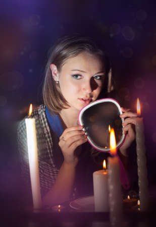 The girl wonders with a mirror in a dark room photo
