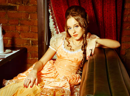 costume ball: A girl in a ball gown sits in an armchair Stock Photo