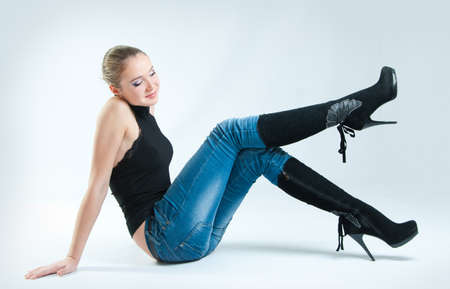 women in jeans: A girl admires his boots with high heels Stock Photo
